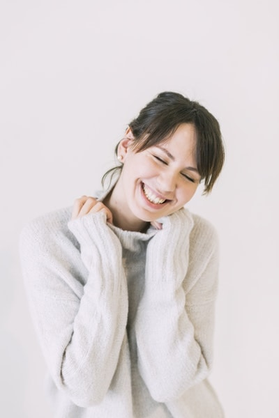 woman in sweater has happy smile